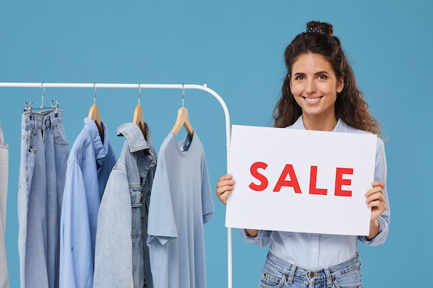 Portrait of young saleswoman smiling while selling jeans clothes in the shop