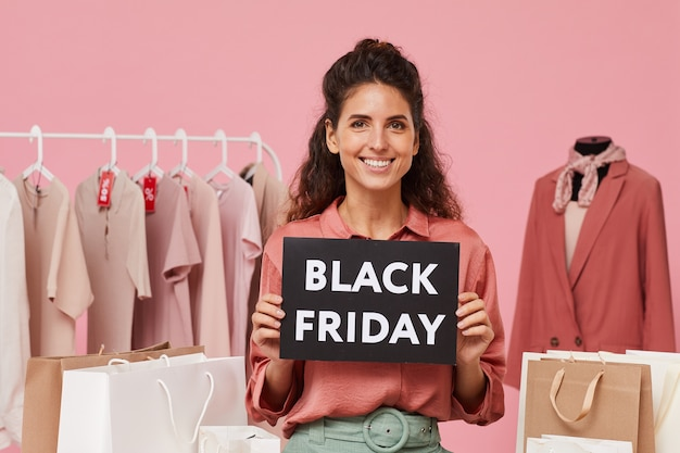 Portrait of young saleswoman smiling with black friday placard in her hands she working in clothes shop
