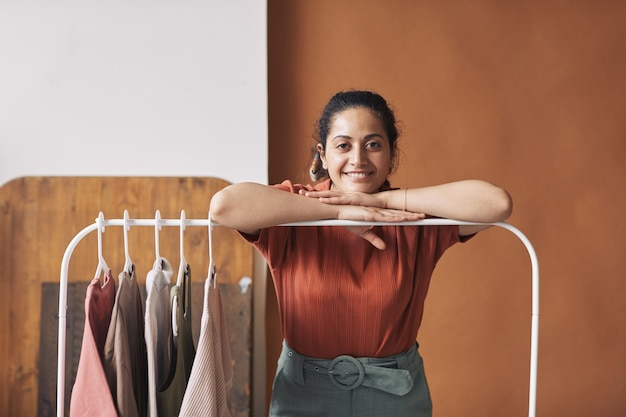 Portrait of young saleswoman standing near the rack with new clothes and smiling at camera she working in the shop