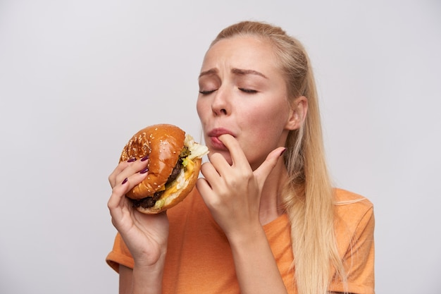 Portrait of young satisfied blonde female with casual hairstyle tasting her fresh hamburger with great pleasure and keeping eyes closed, standing against white background