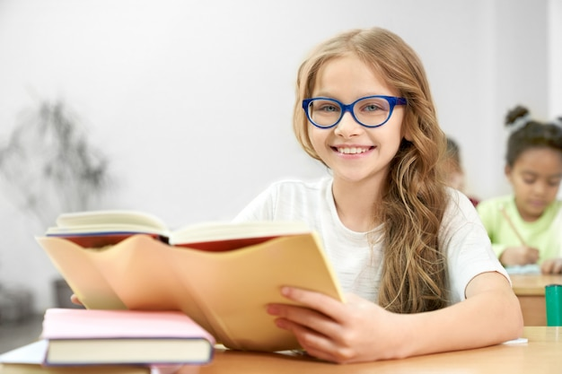 Portrait of young schoolgirl in blue glasses with opened book in classroom.