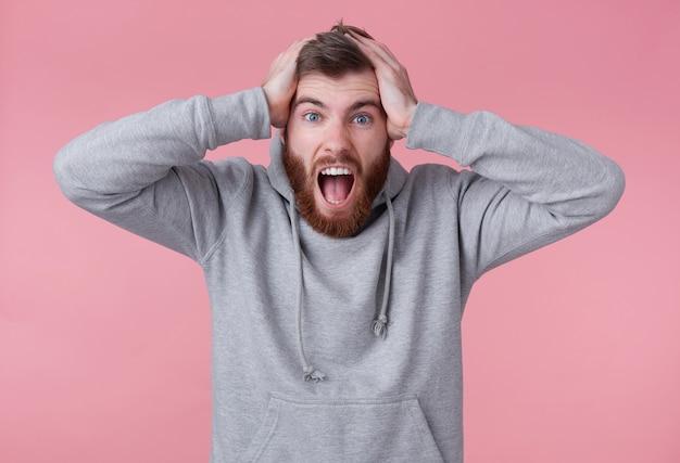 Ritratto di giovane uomo barbuto rosso scioccato urlante in felpa con cappuccio grigia, sembra dispiaciuto, tiene la testa, la sua squadra preferita ha perso. sorge su sfondo rosa e con la bocca spalancata.