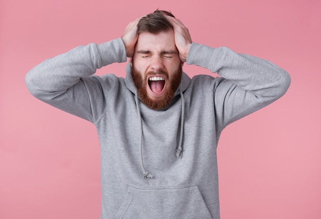 Portrait of young screaming shocked red bearded man in gray hoodie, looks evil and displeased , closed eyes andd holds head, stands over pink background and with wide open mouth.