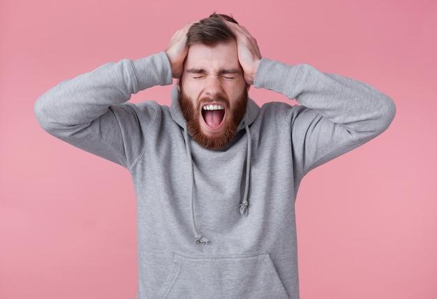Ritratto di giovane uomo barbuto rosso scioccato urlante in felpa con cappuccio grigia, sembra malvagio e dispiaciuto, gli occhi chiusi e tiene la testa, si trova su sfondo rosa e con la bocca spalancata.