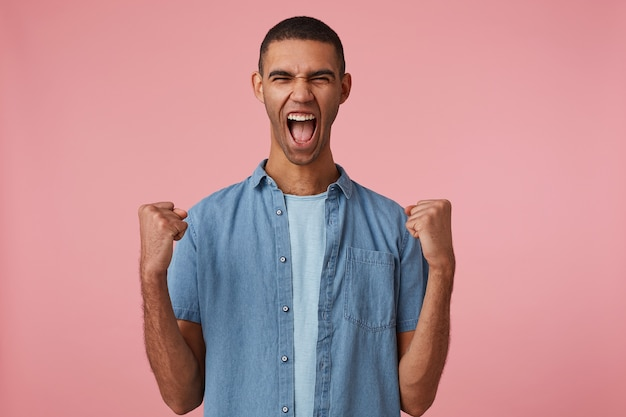 Portrait of young screaming young attractive dark skinned guy in checkered shirt, with fists up and closed eyes, rejoices his favorite teams, stands over pink background.