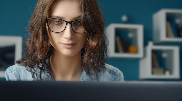 Portrait of young serene woman with loose curly hair wearing eyeglasses looking at computer screen