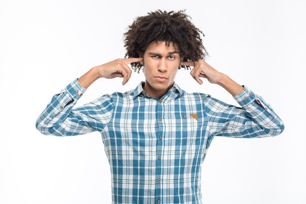 Portrait of a young serious afro american man covering his ears isolated on a white wall