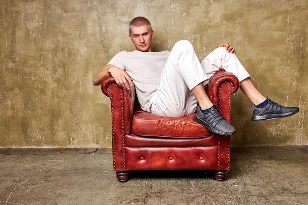 Portrait of young serious caucasian man in white casual wear sitting on leather sofa chair