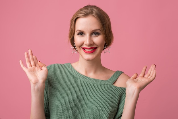 Portrait of young sexy beautiful woman isolated on pink background, smiling, elegant style, red lips, spring fashion trend, happy face expression, looking in camera, positive emotion, holding hands up