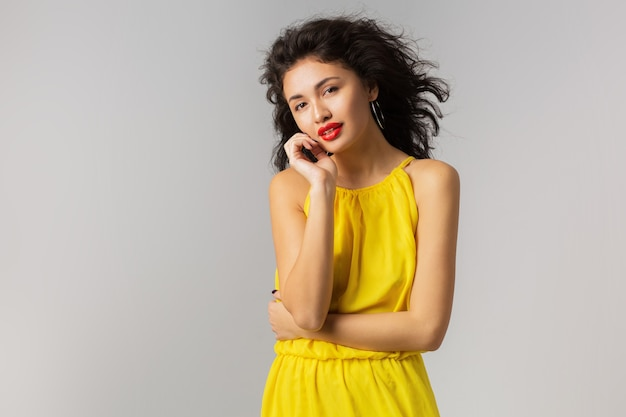 Portrait of young sexy brunette woman in yellow dress, touching her face, red lips, curly hair waving in wind, summer style, fashion trend, looking in camera, mixed race, isolated, holding hands up