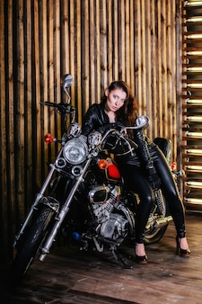 Portrait of young sexy fashion brunette woman in a leather jacket and leather pants, sitting on a motorcycle in studio on a background of wooden wall