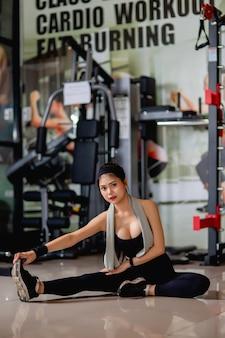 운동복과 스마트 워치를 입고 세로 젊은 섹시한 여자가 바닥에 앉아 피트니스 체육관에서 운동하기 전에 그녀의 다리 근육을 streching,