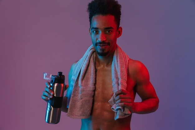 Portrait of young shirtless african american man posingwith thermos bottle and towel isolated over violet wall