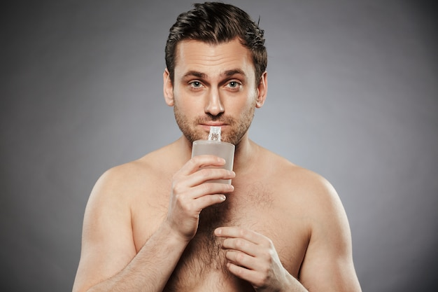 Portrait of a young shirtless man smelling aftershave