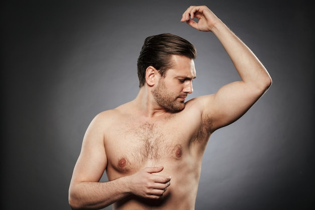 Portrait of a young shirtless man smelling his armpit
