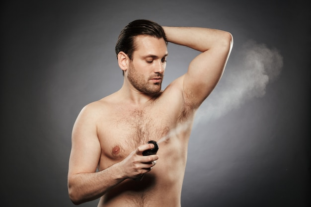 Portrait of a young shirtless man spraying deodorant