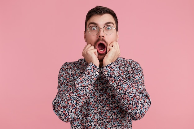 Portrait of young shocked bearded man in glasses, wearing in colorful shirt, with wide open mouth, bites finger nails. isolated over pink background. people and emotions concept.