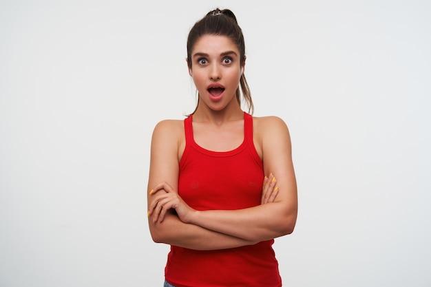 Ritratto di giovane donna bruna carina scioccata indossa in maglietta rossa. si trova su sfondo bianco con le braccia incrociate e guarda la telecamera con la bocca aperta.