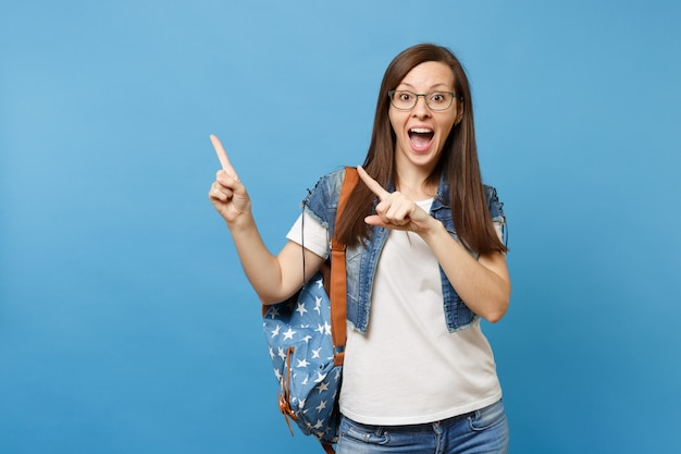 Portrait of young shocked exited woman student with backpack wearing glasses pointing index finger aside on copy space isolated on blue background. education in high school university college concept.