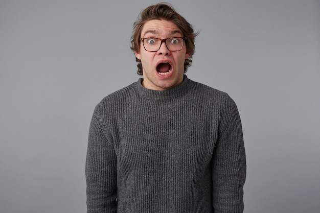 Portrait of young shocked guy with glasses, stands over gray background with wide open mouth and eyes, with surprised expression, looks scared.