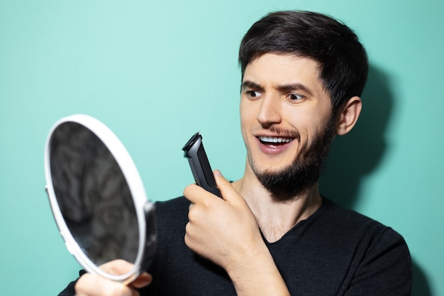 Portrait of young shocked guy with half shaved face holding trimmer and mirror in hands