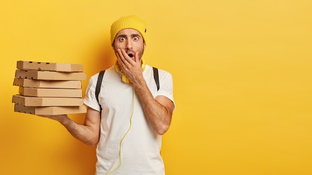 Portrait of young shocked male delivery worker holds stack of pizza boxes, dressed casually, covers opened mouth, stands against yellow wall