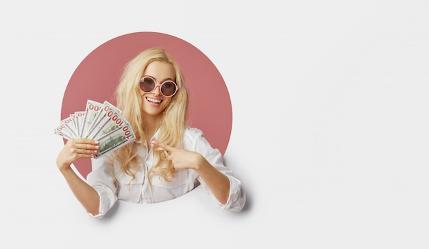 Portrait of a young shocked woman with a bundle of banknotes and text sale. peeping through the white hole in the wallfunny face with open mouth. wow concept