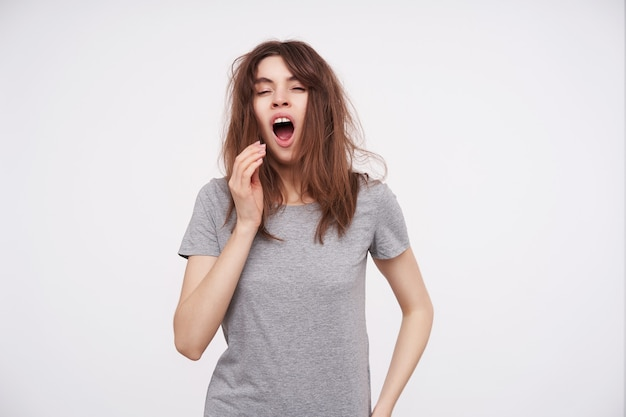 Portrait of young sleepy brown haired female dressed in basic grey t-shirt raising hand to her mouth while yawning with closed eyes, isolated on white