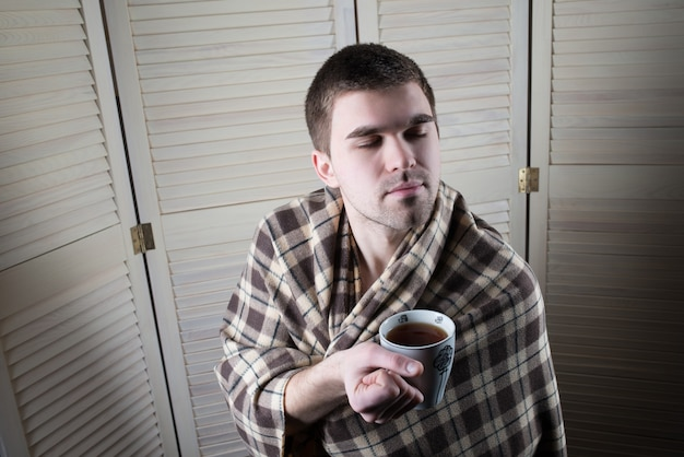 Portrait of a young sleepy man wrapped in a plaid holding a mug of tea in his hands on the surface of the wardrobe