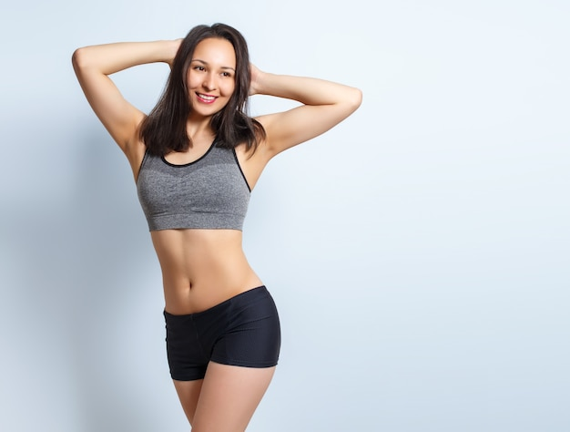 Portrait of a young slim fitness woman on a blue background