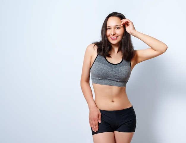 Portrait of a young slim fitness woman on a white background