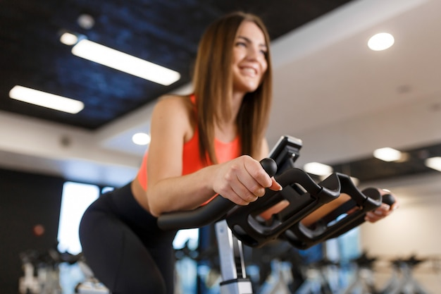 Portrait of young slim woman in sportwear workout on exercise bike in gym. sport and wellness lifestyle