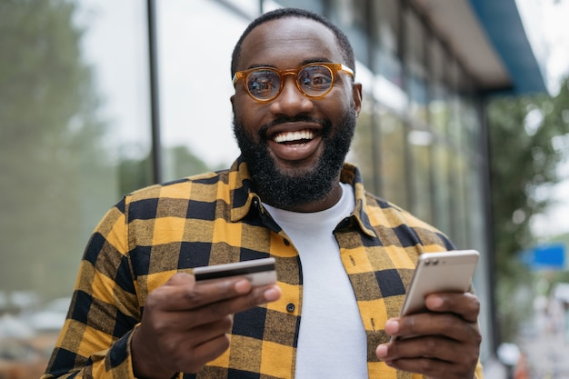 Portrait of young smiling african american man holding credit card, shopping online