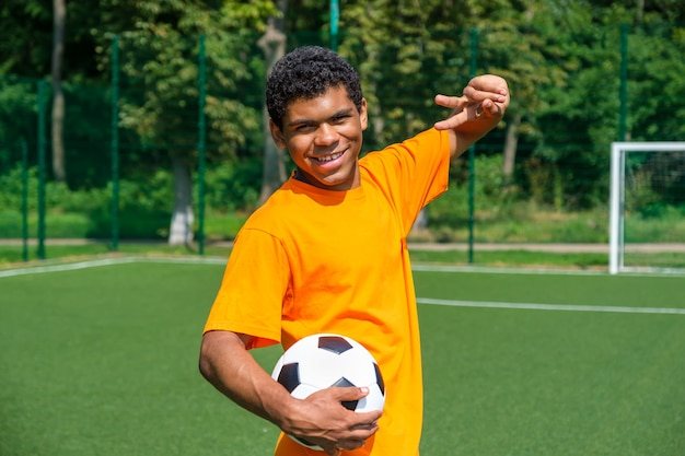 Portrait of young smiling african-american man holding soccer ball and showing victory sign while standing on sports court outdoors against soccer goal