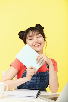 Portrait of young smiling asian woman with book excited to take new class online