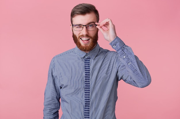 Portrait of young smiling attractive bearded man in a striped shirt, holds glasses and winks isolated over pink background.