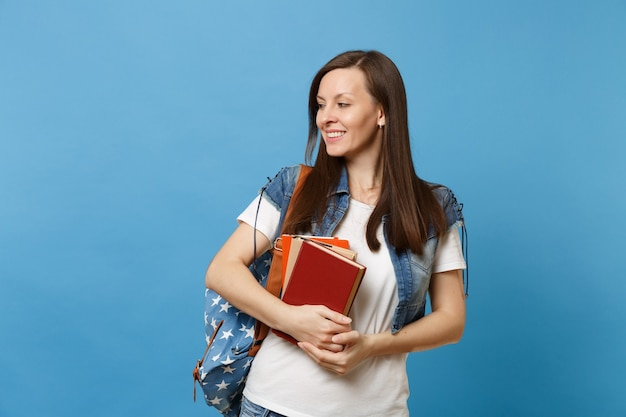 Portrait of young smiling attractive woman student with backpack looking aside and holding school books ready to learn isolated on blue background. education in high school university college concept.