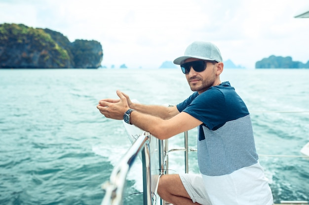 Portrait young smiling bearded man in a cap standing on a yacht and looking at the horizon.