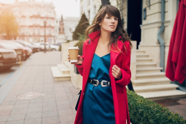 Portrait of young smiling beautiful stylish woman walking in city street in red coat drinking coffee