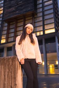 ピンクのニット帽とセーターを着て、冬の街で若い笑顔のブルネットモデルを肖像画