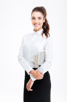 Portrait of a young smiling business woman holding books isolated on white wall