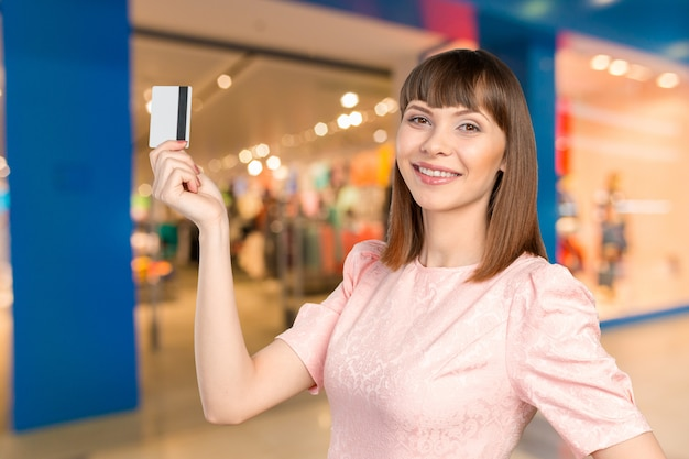 Portrait of young smiling business woman holding credit card