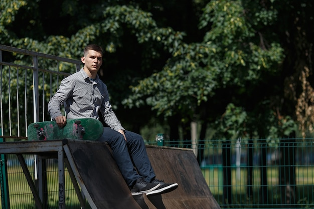 Portrait of young smiling guy dressed in stylish shirt sneakers and pants seated with skateboard in skate park on sunny summer day