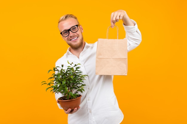 Portrait of a young smiling guy in a white dress shirt and glasses holding a craft bag and a houseplant in a pot on a yellow