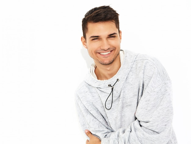 Portrait of young smiling handsome model man dressed in gray casual hoodie clothes posing on white wall. isolated