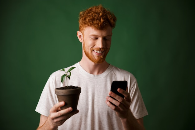 Portrait of young smiling handsome redhead bearded young man, holding spotted plant, looking at mobile phone