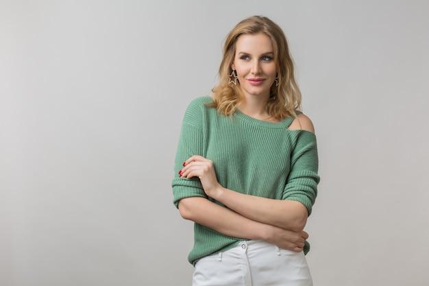 Ritratto di giovane donna attraente felice sorridente, positivo, fiducioso, elegante, stile casual, maglione verde, modello in posa su sfondo bianco studio, isolato, guardando a porte chiuse