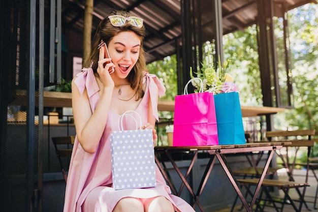 Ritratto di giovane donna attraente felice sorridente che si siede nella caffetteria parlando al telefono con borse della spesa, vestito di moda estiva, stile hipster, vestito di cotone rosa, volto sorpreso