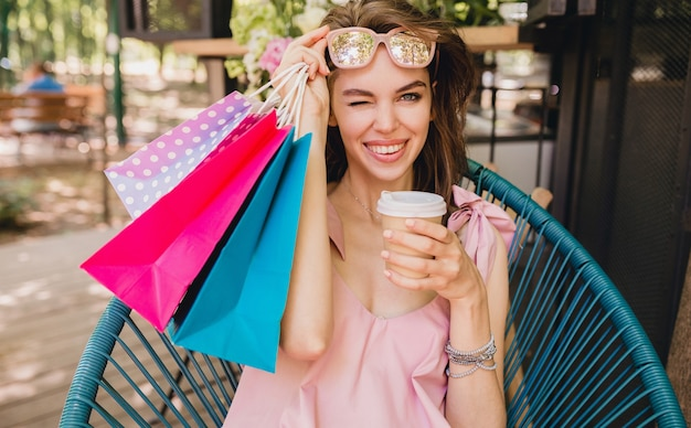 Portrait of young smiling happy pretty woman with excited face expression sitting in cafe with shopping bags drinking coffee, summer fashion outfit, hipster style, pink cotton dress, trendy apparel
