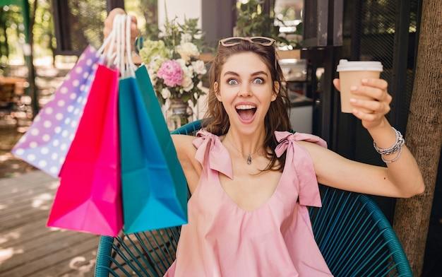 Ritratto di giovane donna graziosa felice sorridente con espressione del viso eccitato seduto al bar con borse della spesa che bevono caffè, vestito di moda estiva, stile hipster, vestito di cotone rosa, abbigliamento alla moda